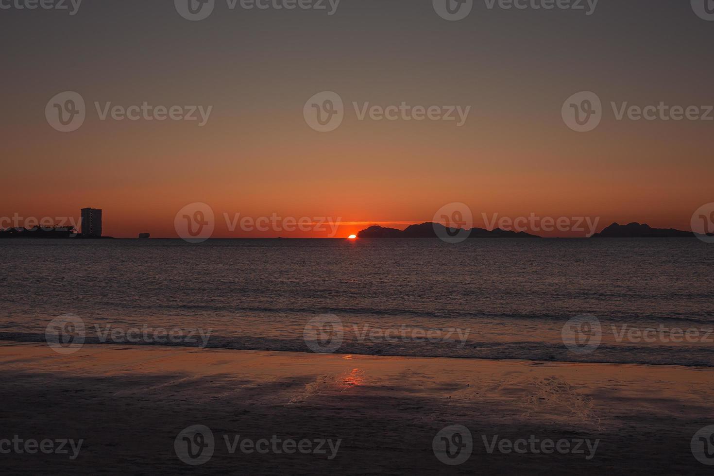zon verschuilt zich achter de eilanden foto