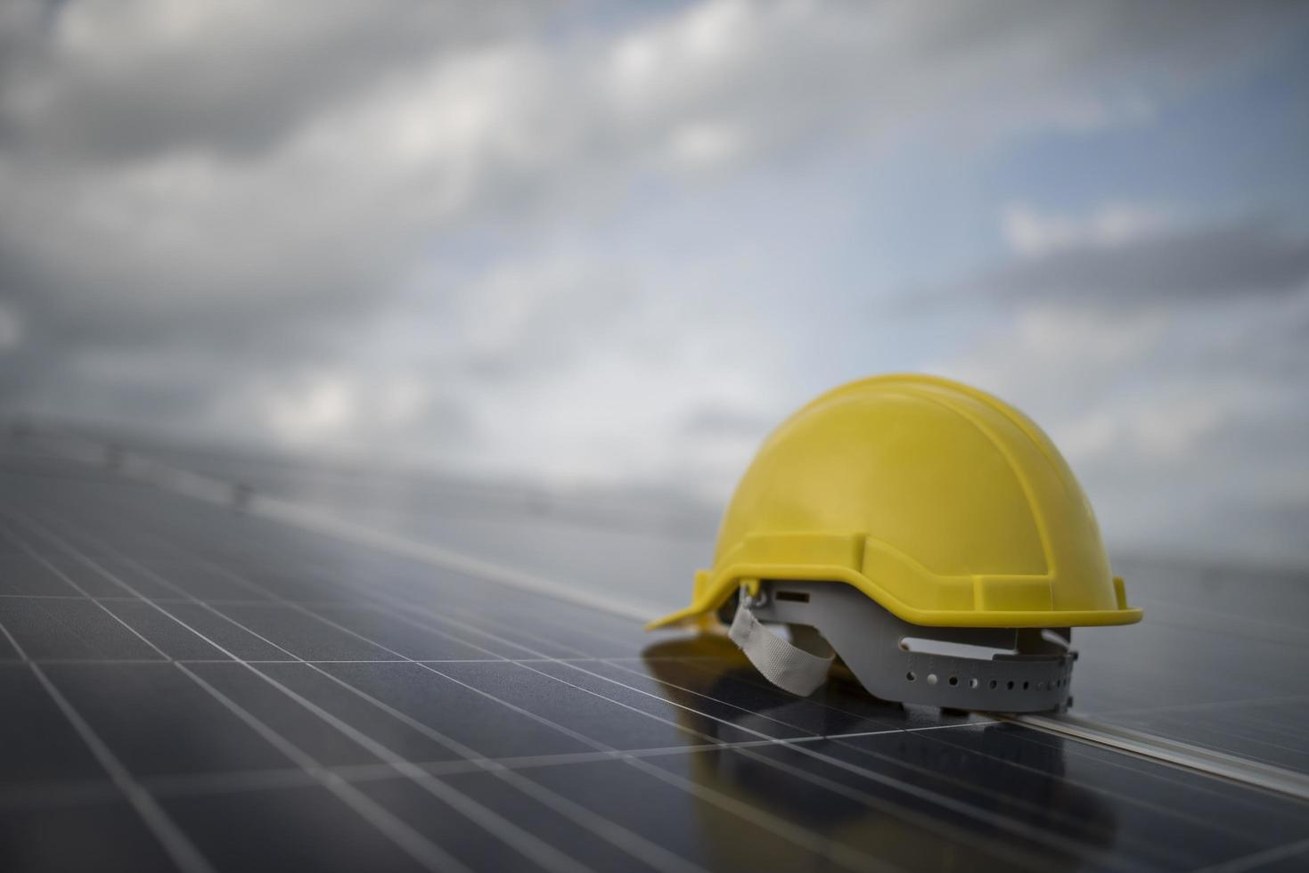 gele veiligheidshelm op zonnepaneel foto