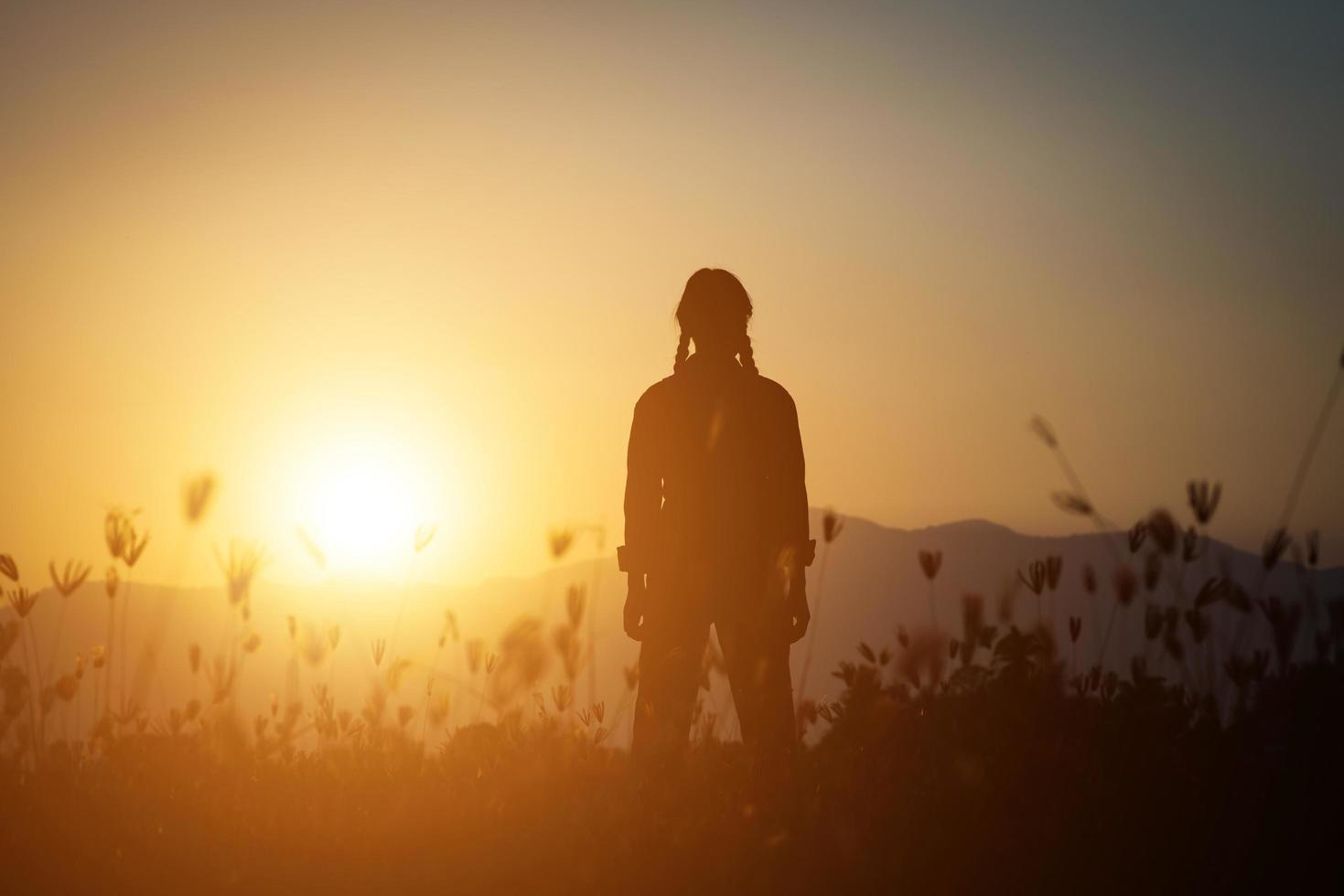 silhouet van een vrouw die bidt over een mooie hemelachtergrond foto