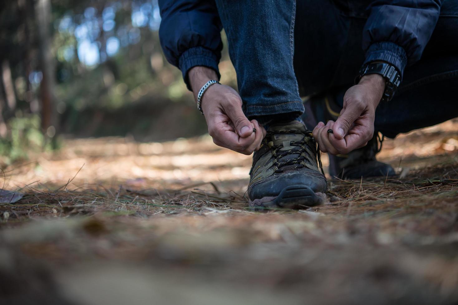 jonge wandelaar man knoopt zijn veters vast tijdens het backpacken in het bos foto