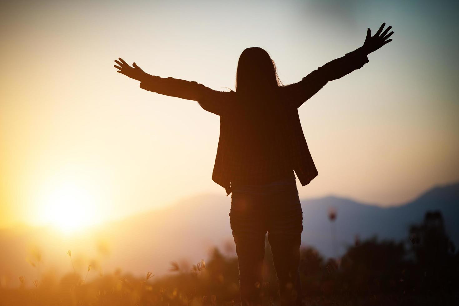 silhouet van een vrouw die bidt over mooie hemelachtergrond foto