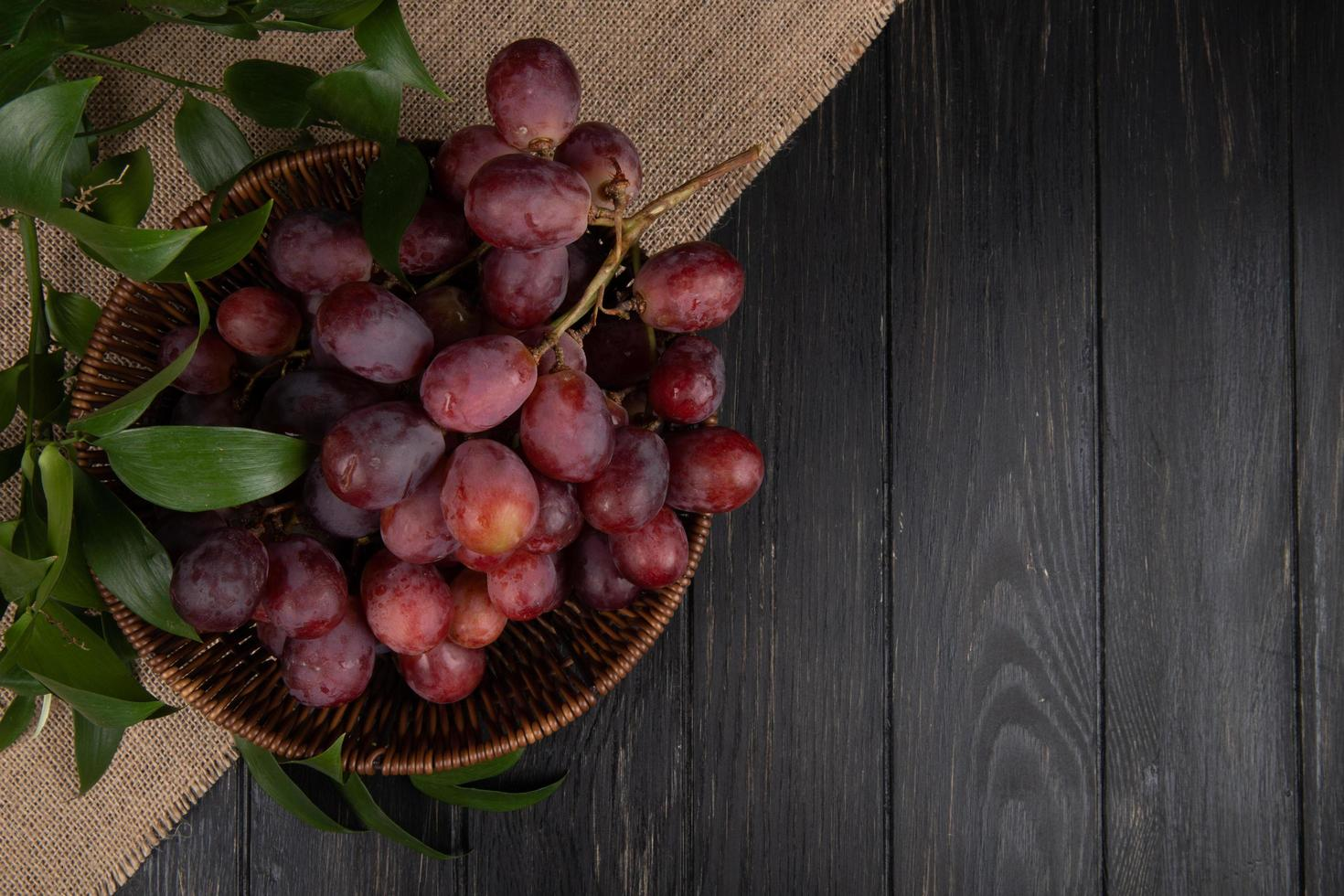 bovenaanzicht van een bos van rode druiven in een rieten mand op een houten achtergrond foto