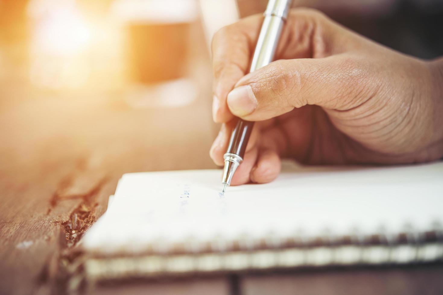 vrouw schrijven in notitieblok foto