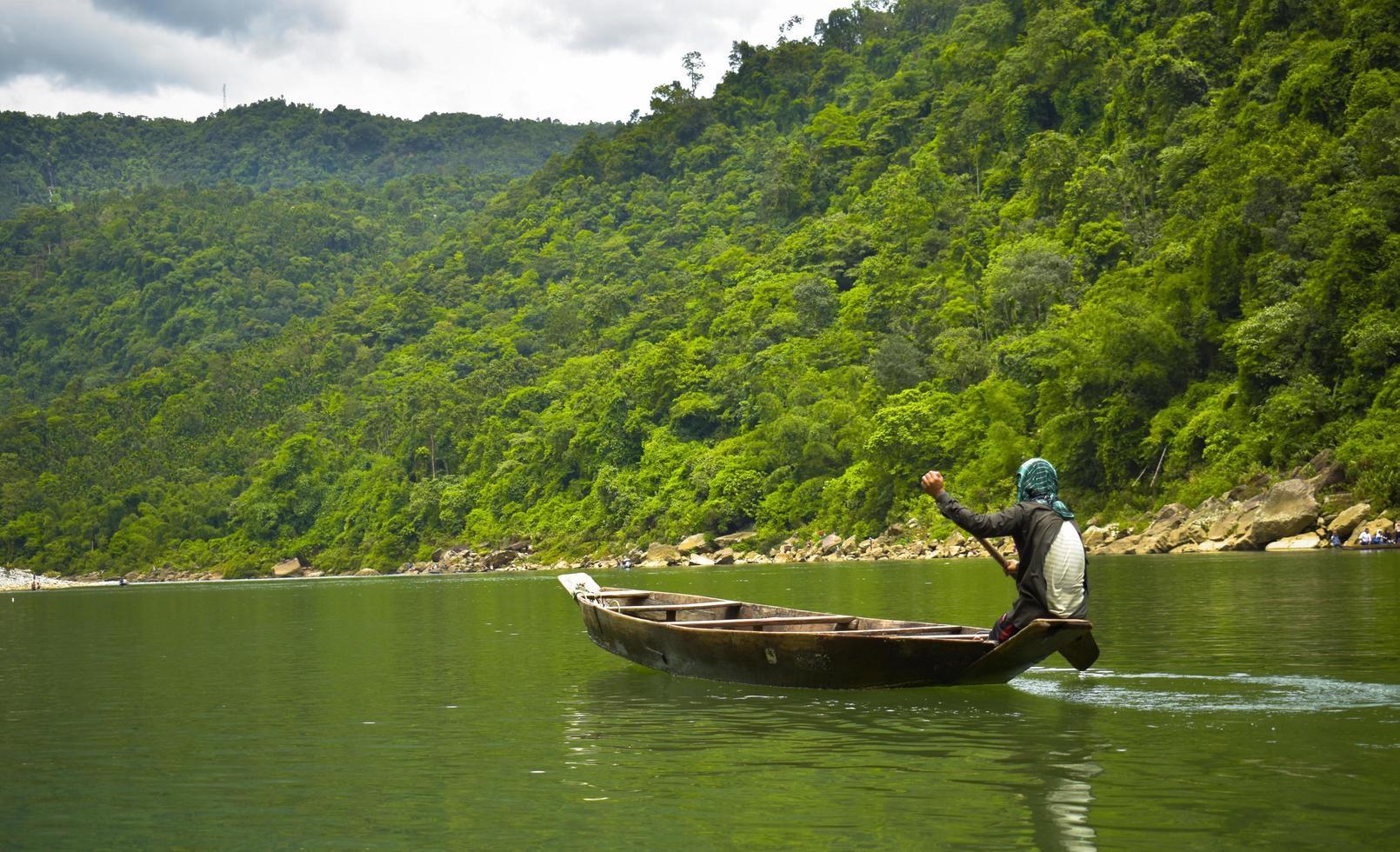 mannen roeien een boot in de buurt van groene heuvel overdag foto