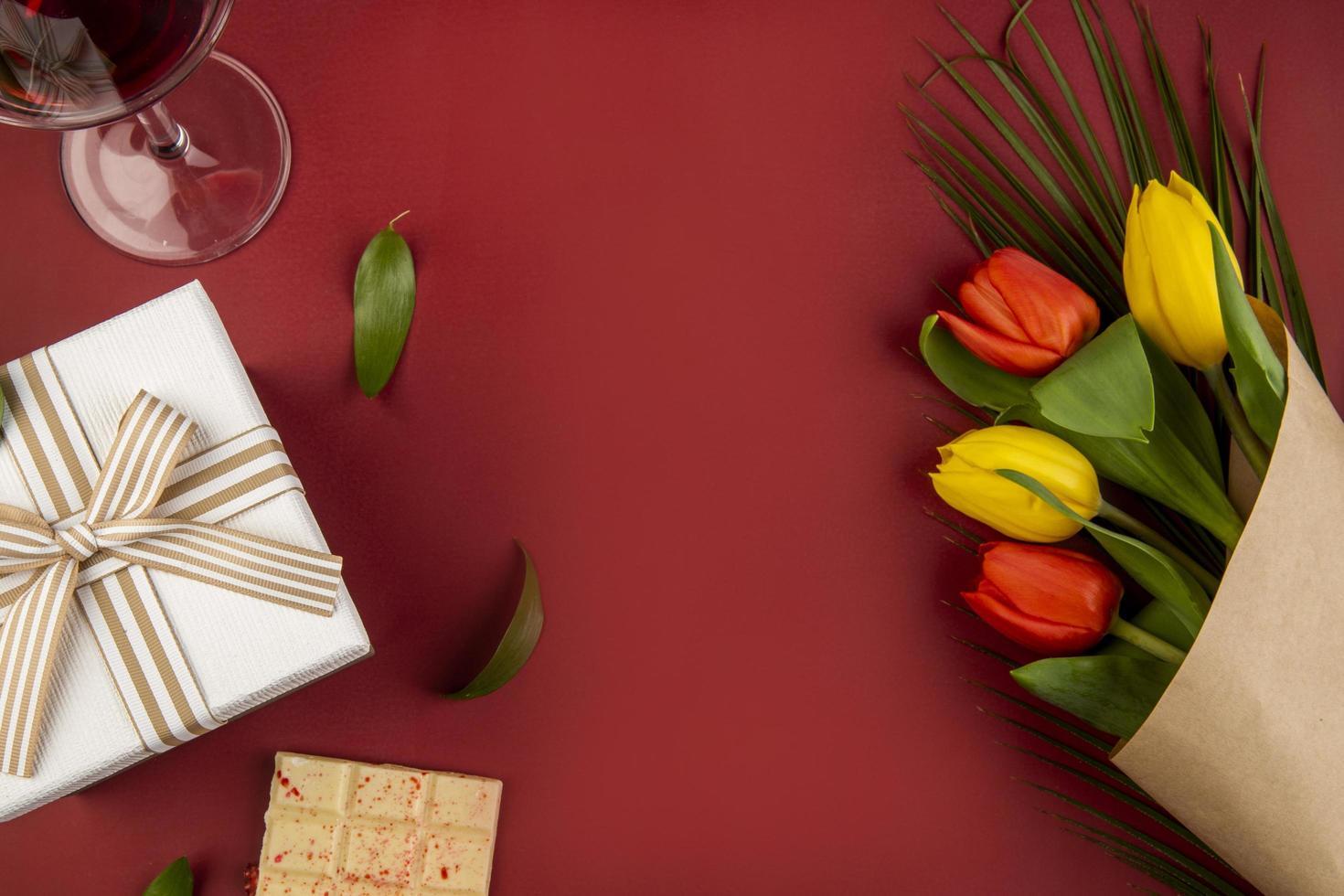 bovenaanzicht van een boeket met wijn en een cadeau op een rode achtergrond foto