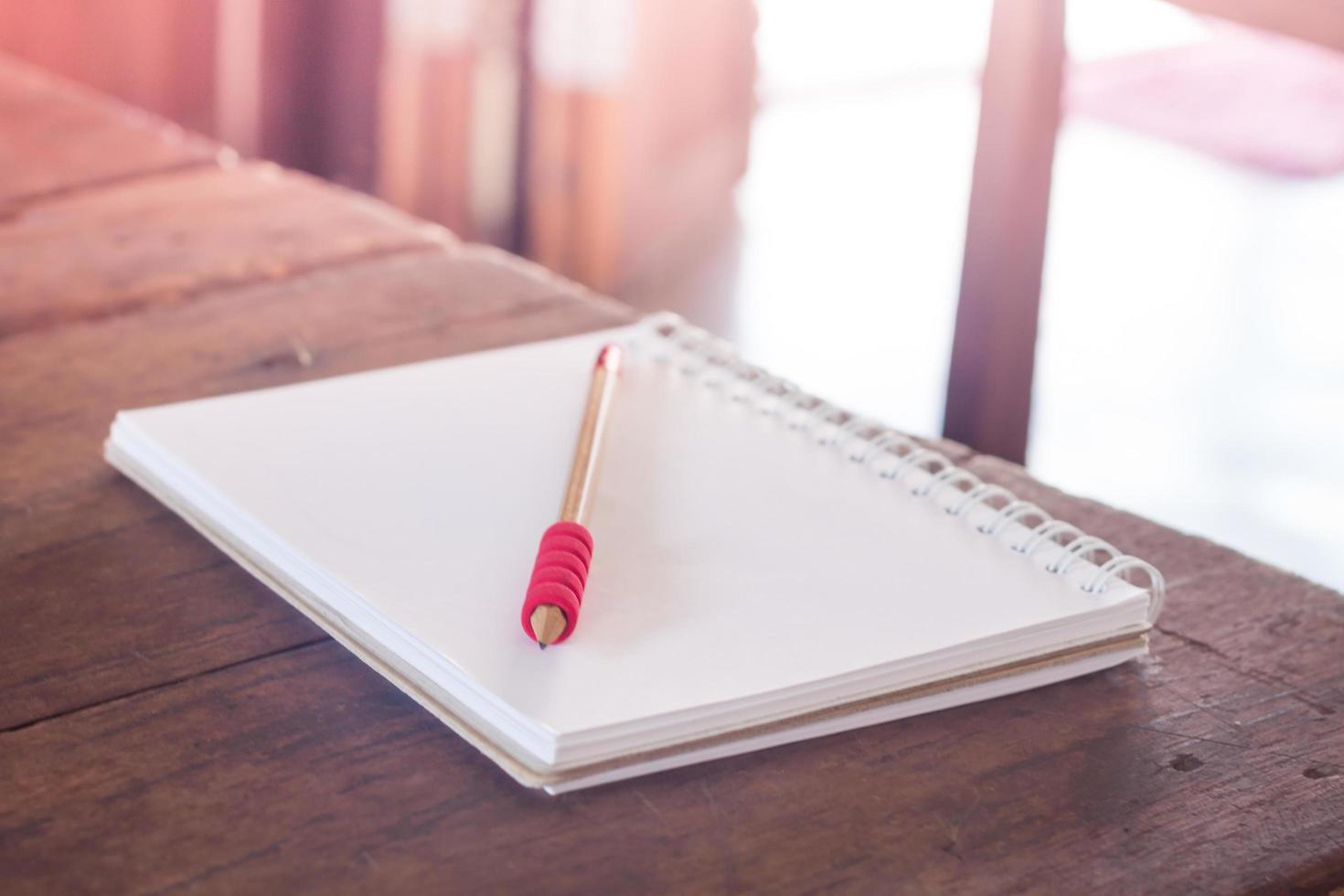 zonlicht op een tafel met een notitieboekje en potlood foto