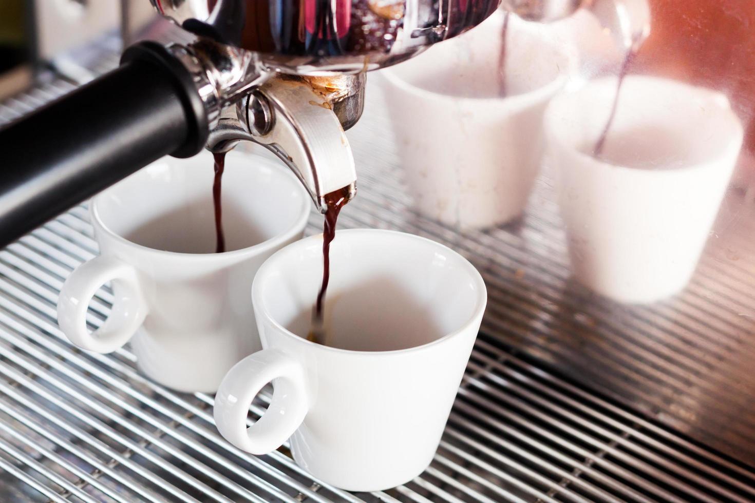 espresso wordt in kopjes gegoten foto