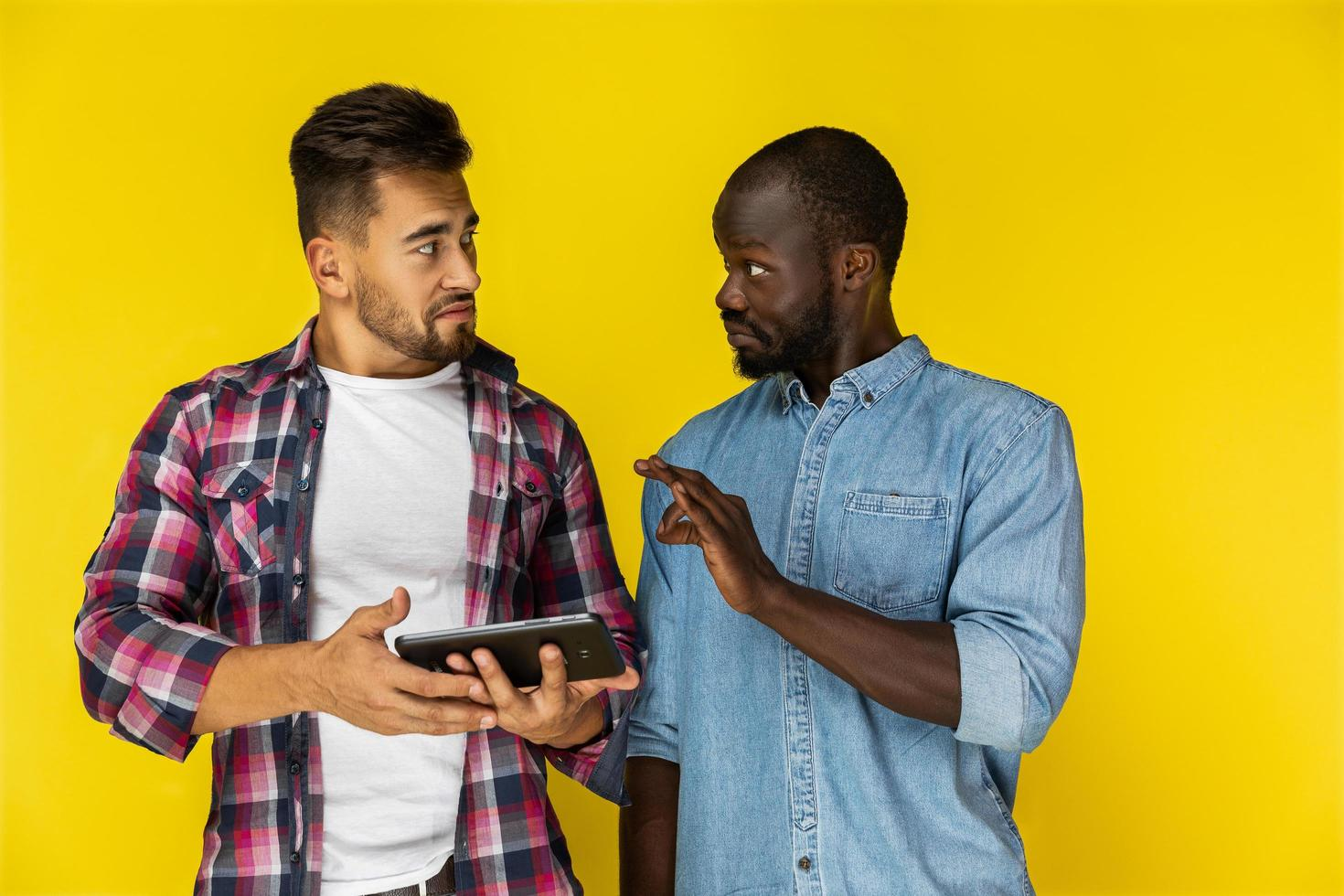twee jongens praten en houden een tablet vast foto