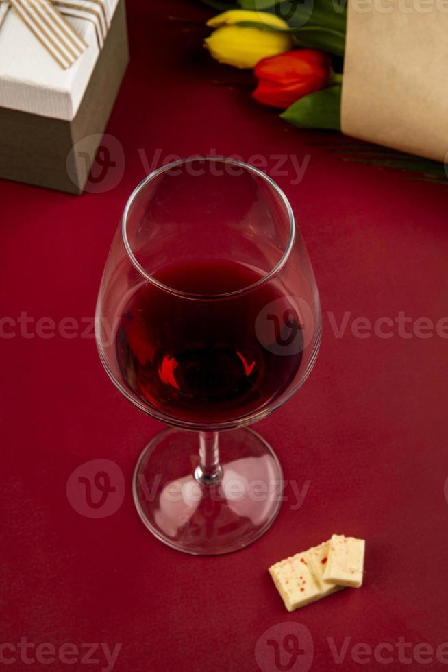 glas wijn met een geschenk en bloemen foto