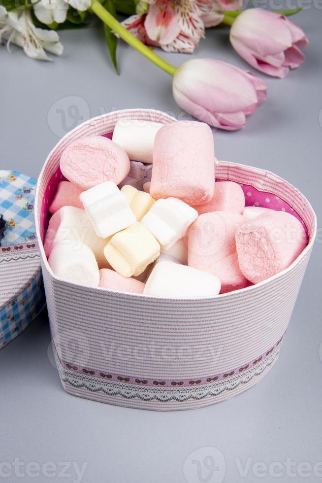 roze en witte snoepjes in een hartvormig doosje foto