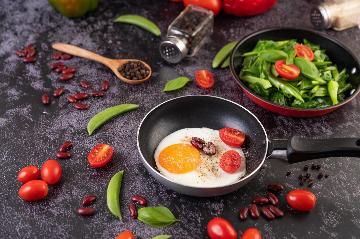 gebakken eieren in een koekenpan met tomaat foto