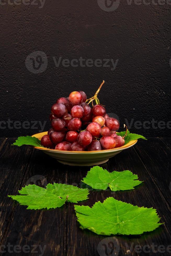 kom met rode druiven foto