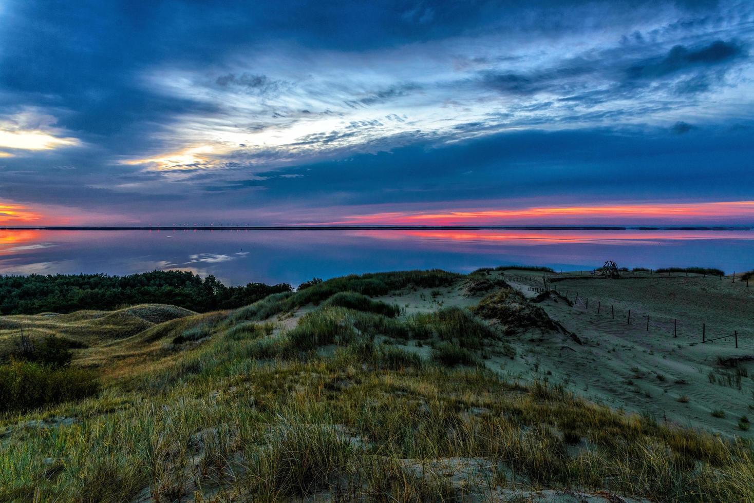 waterlichaam en duinen tijdens zonsondergang foto
