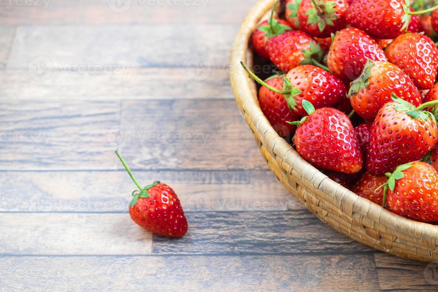 kom met aardbeien op een tafel foto