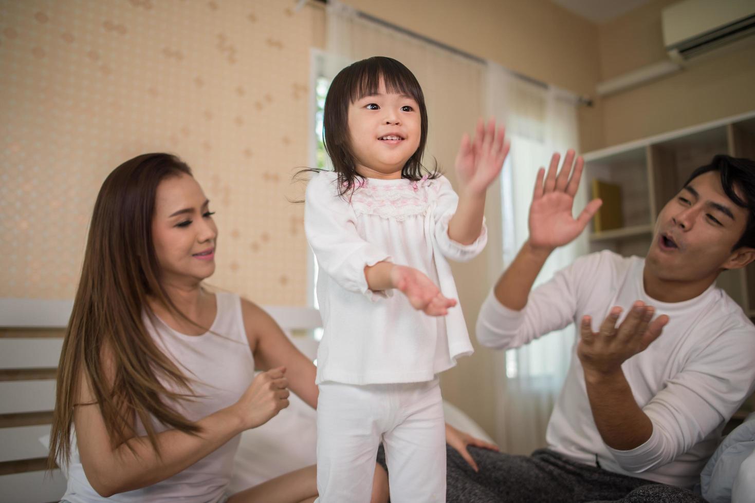 gelukkig kind met ouders die thuis spelen foto