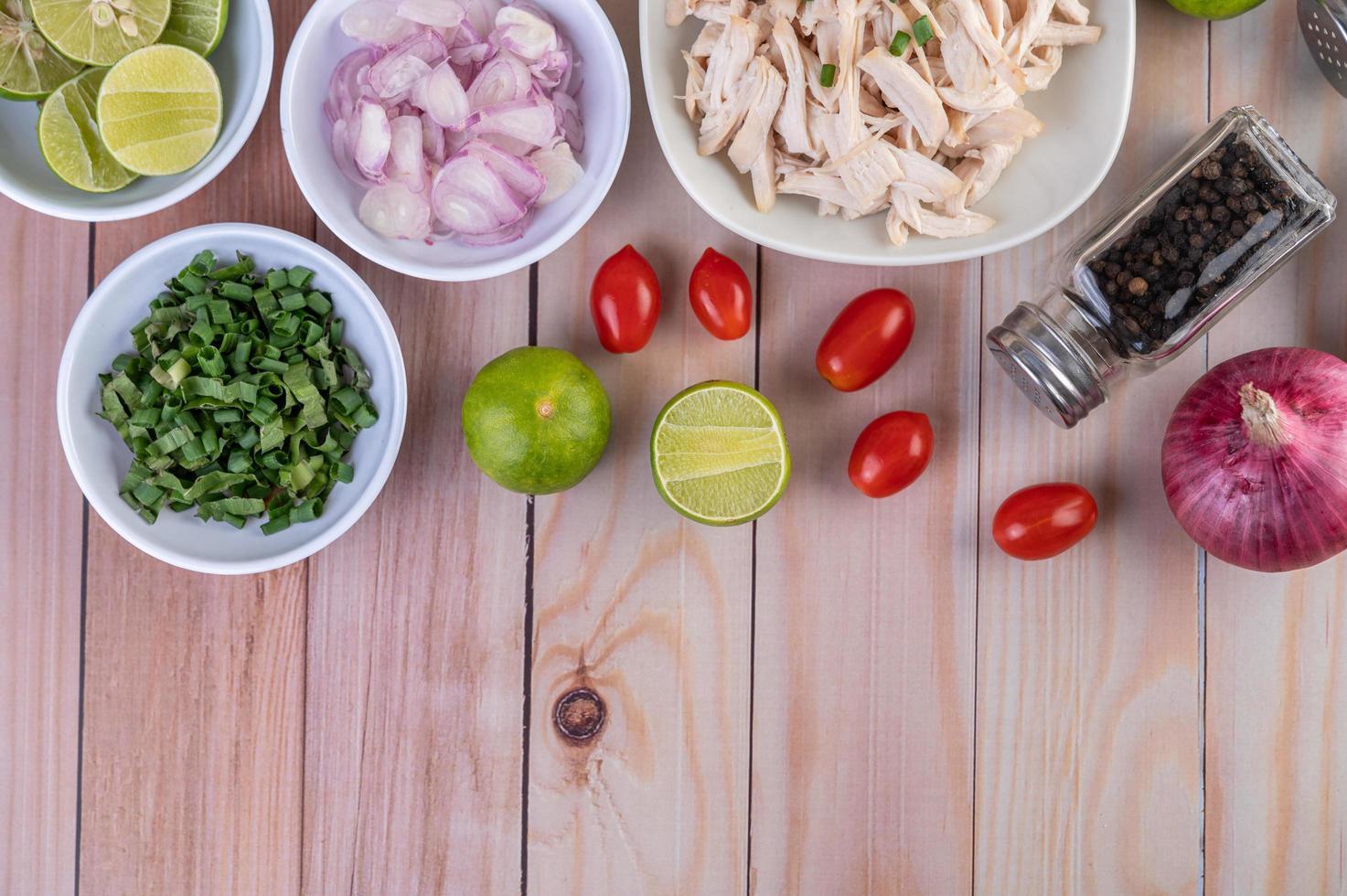 gekookte stukjes kip met groenten en kruiden op een houten tafel foto