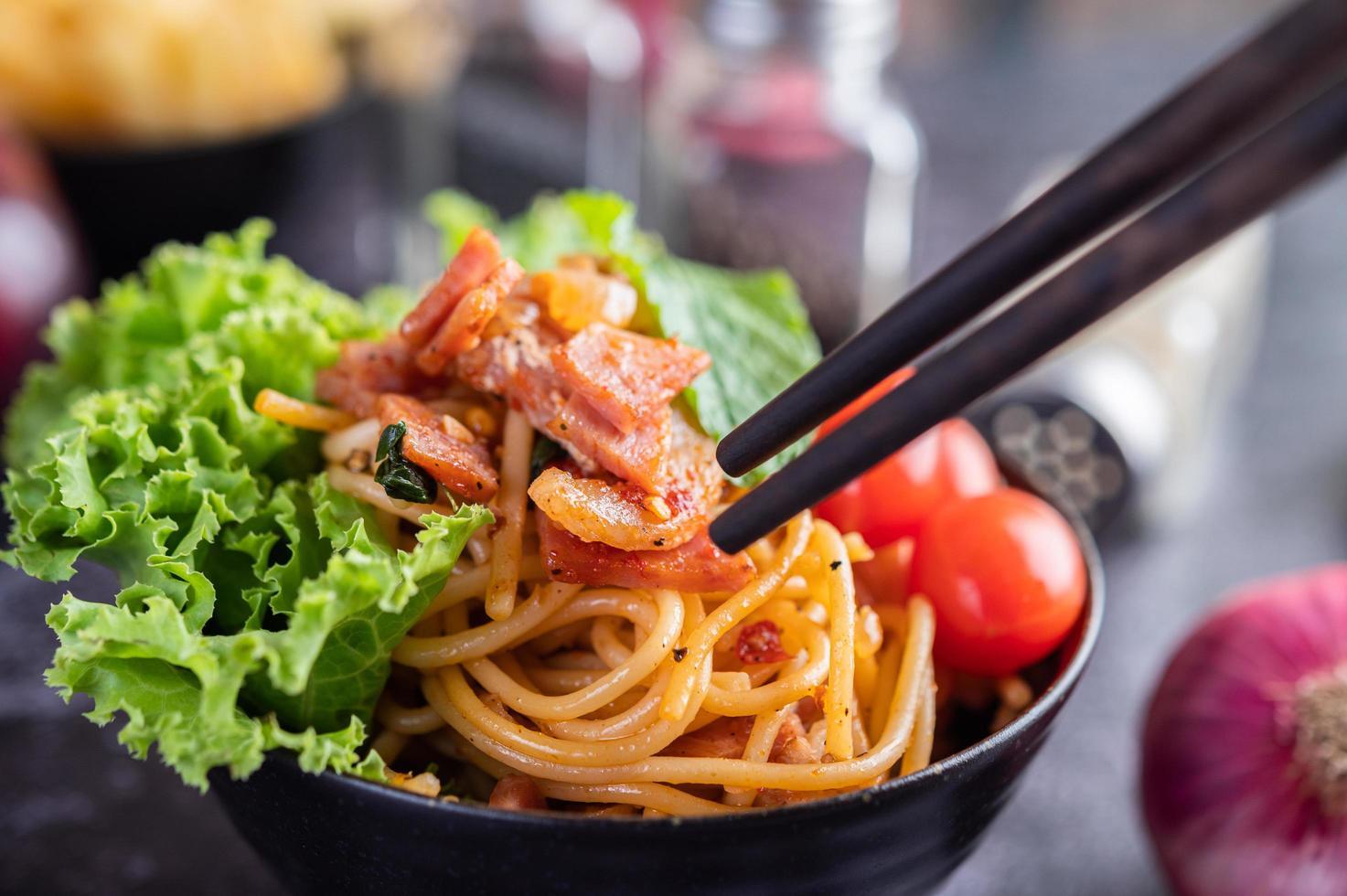 spaghetti in een zwarte kop met tomaten en sla. foto