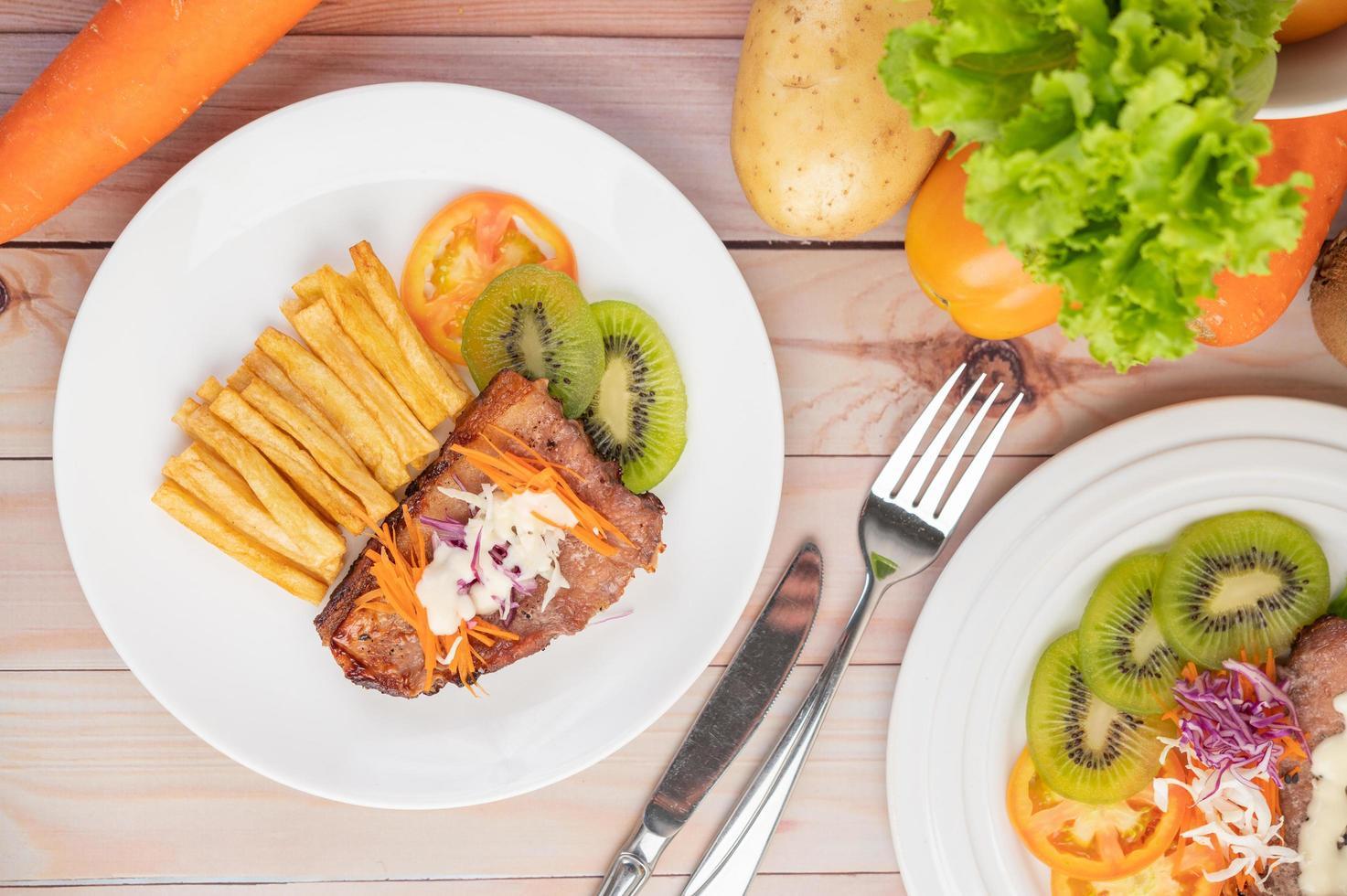visbiefstuk met frietjes, fruit en groenten foto