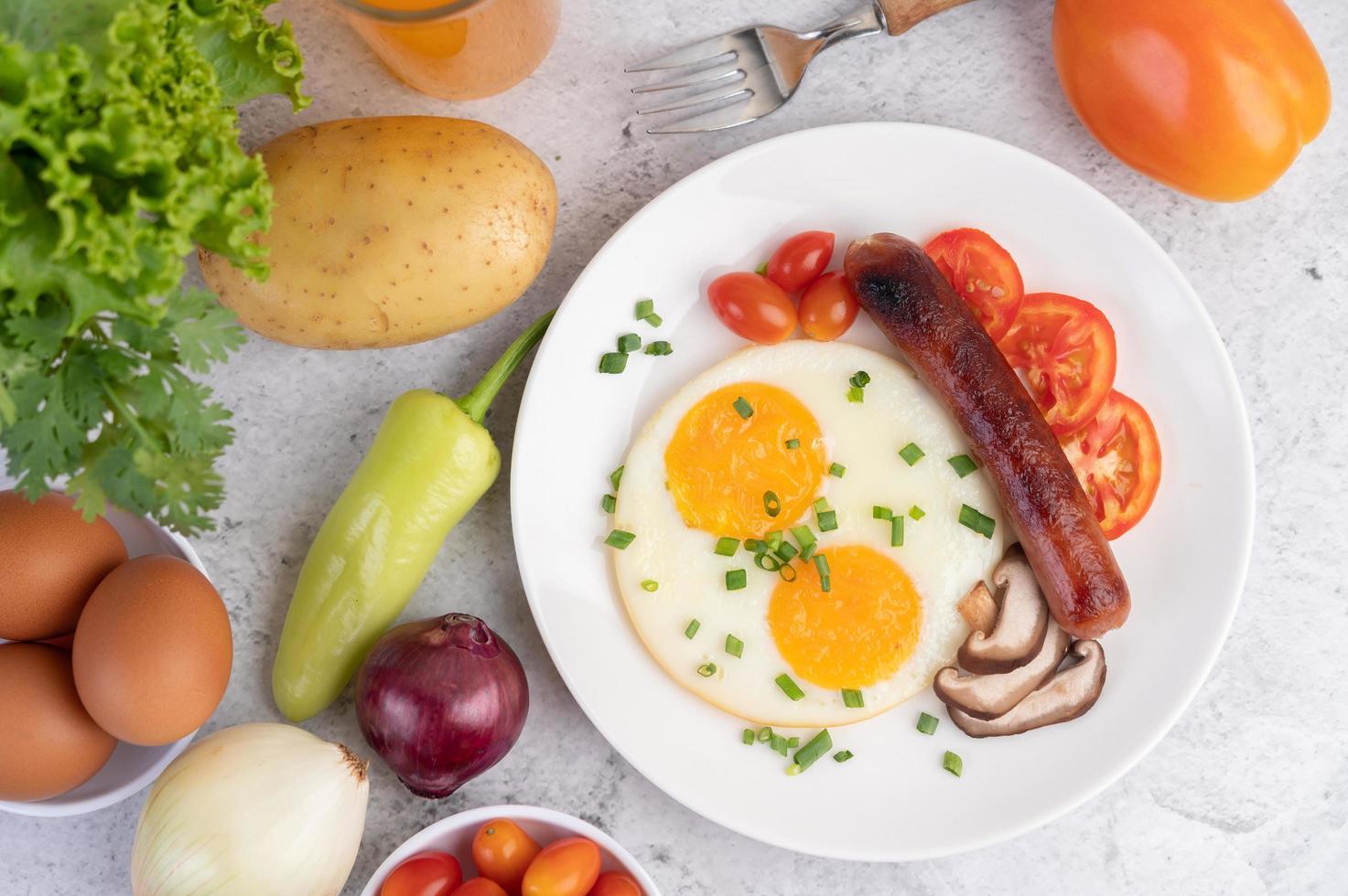 ontbijtbord met gebakken eieren, tomaten, chinese worst en champignons foto