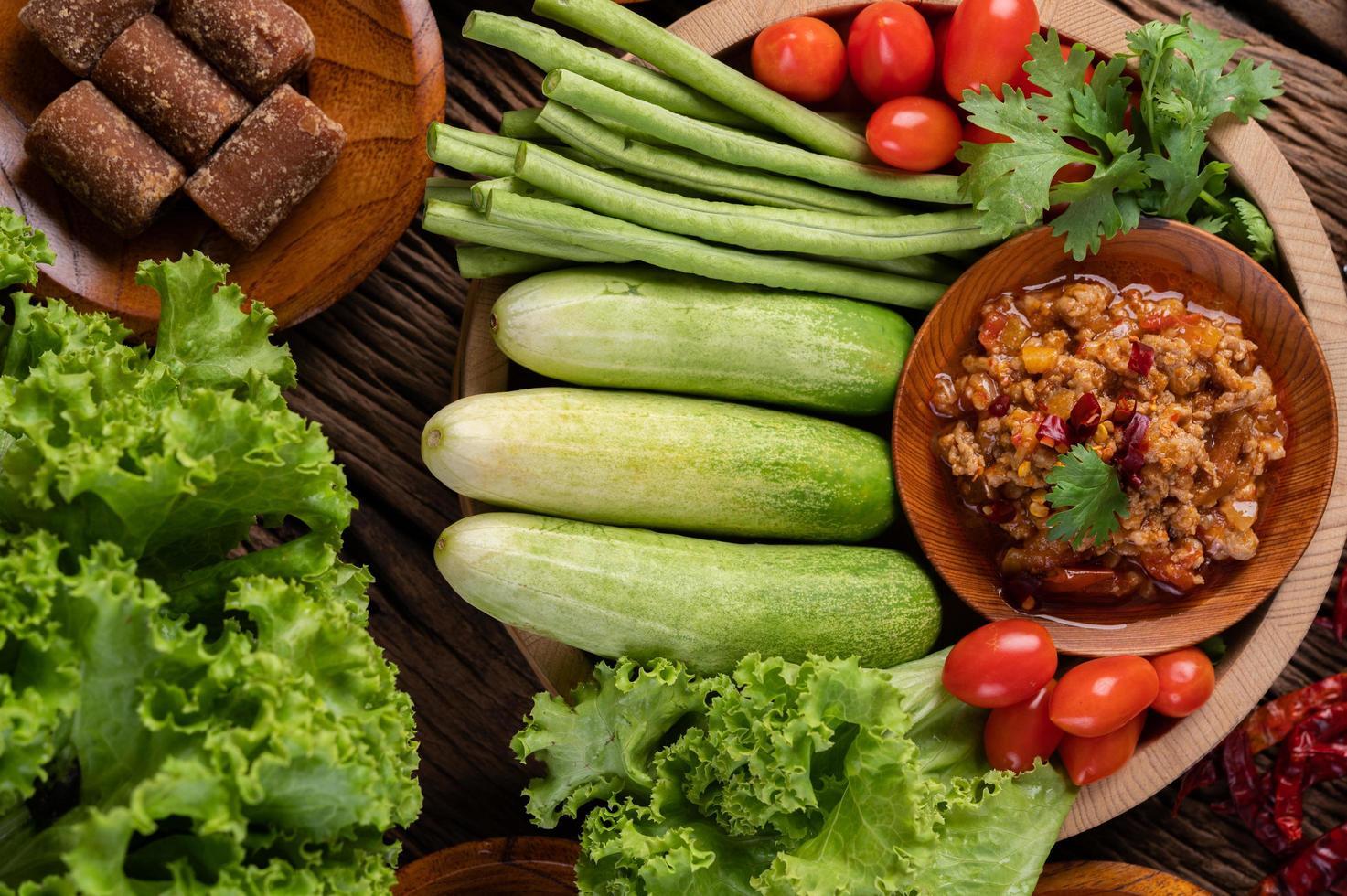 zoet varkensvlees in een houten kom met ingrediënten foto