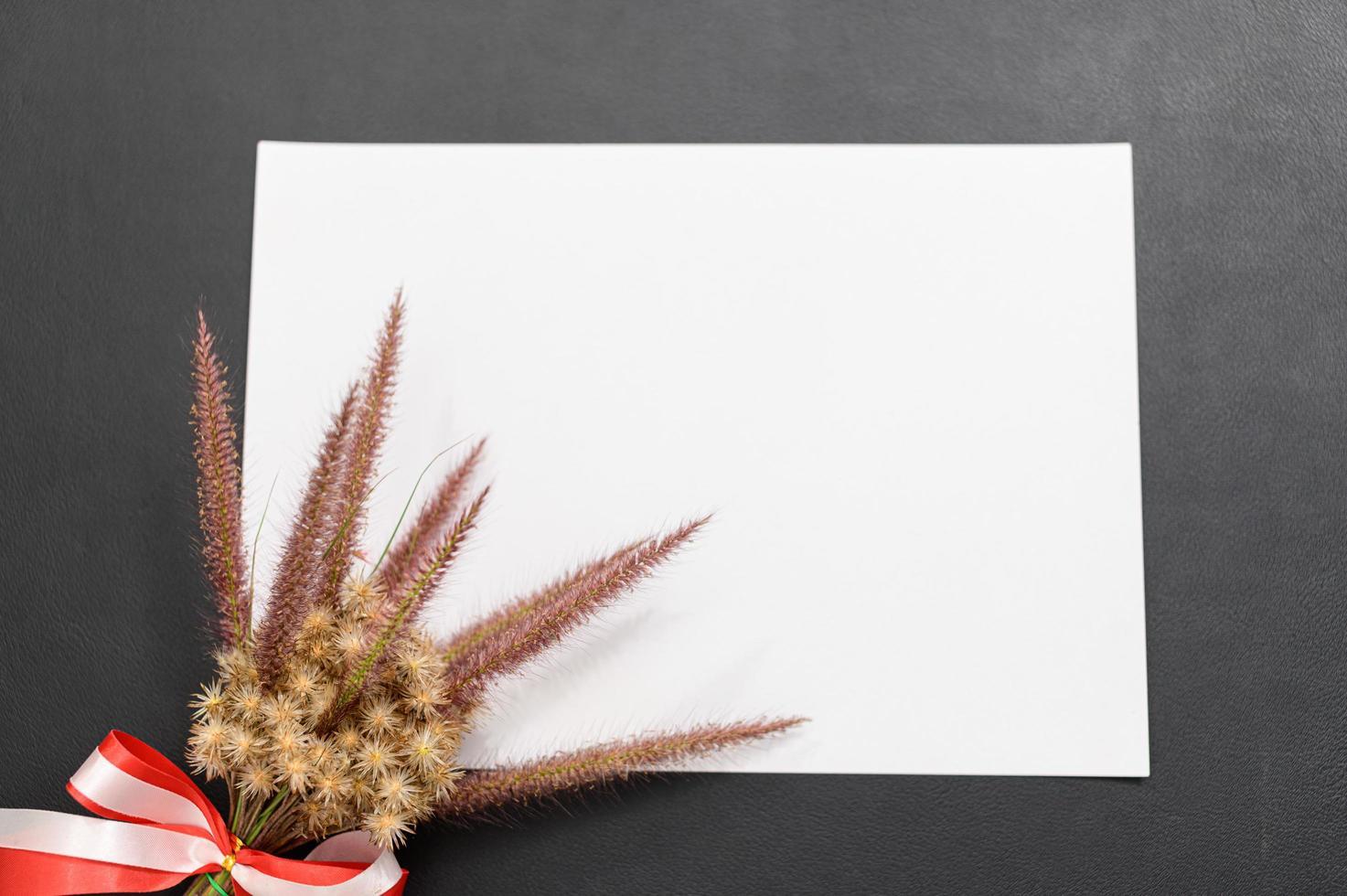 blanco papier en bloem op het bureau foto