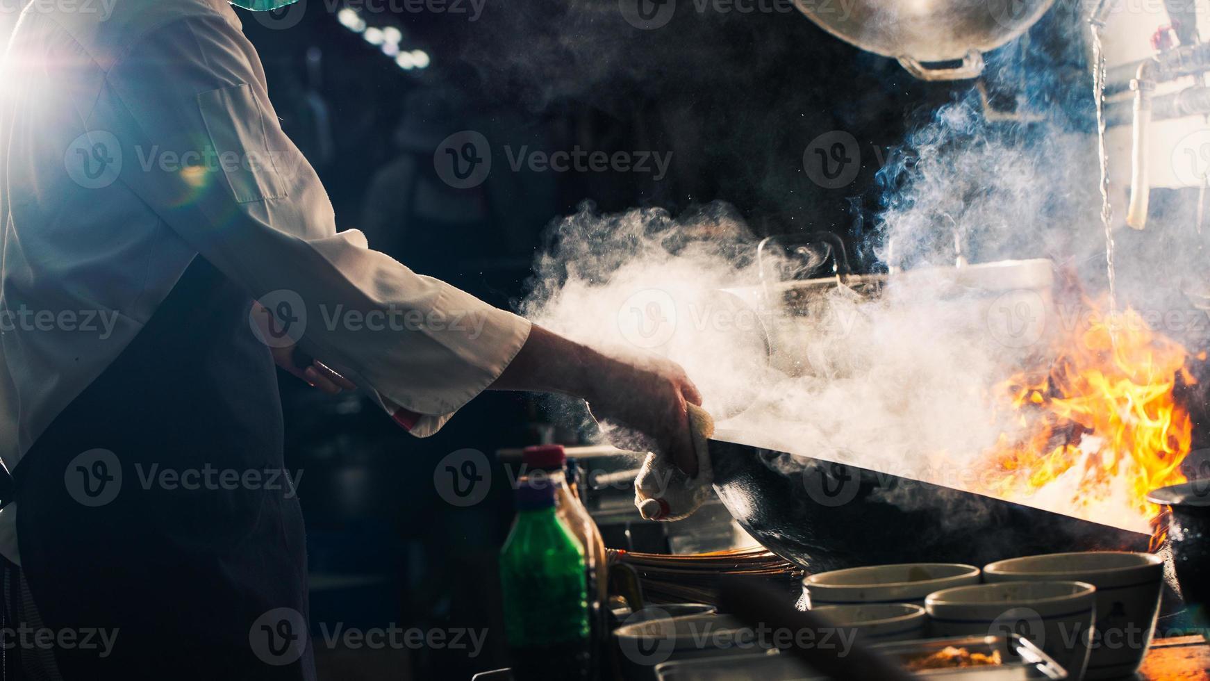chef roerbakken in wok foto