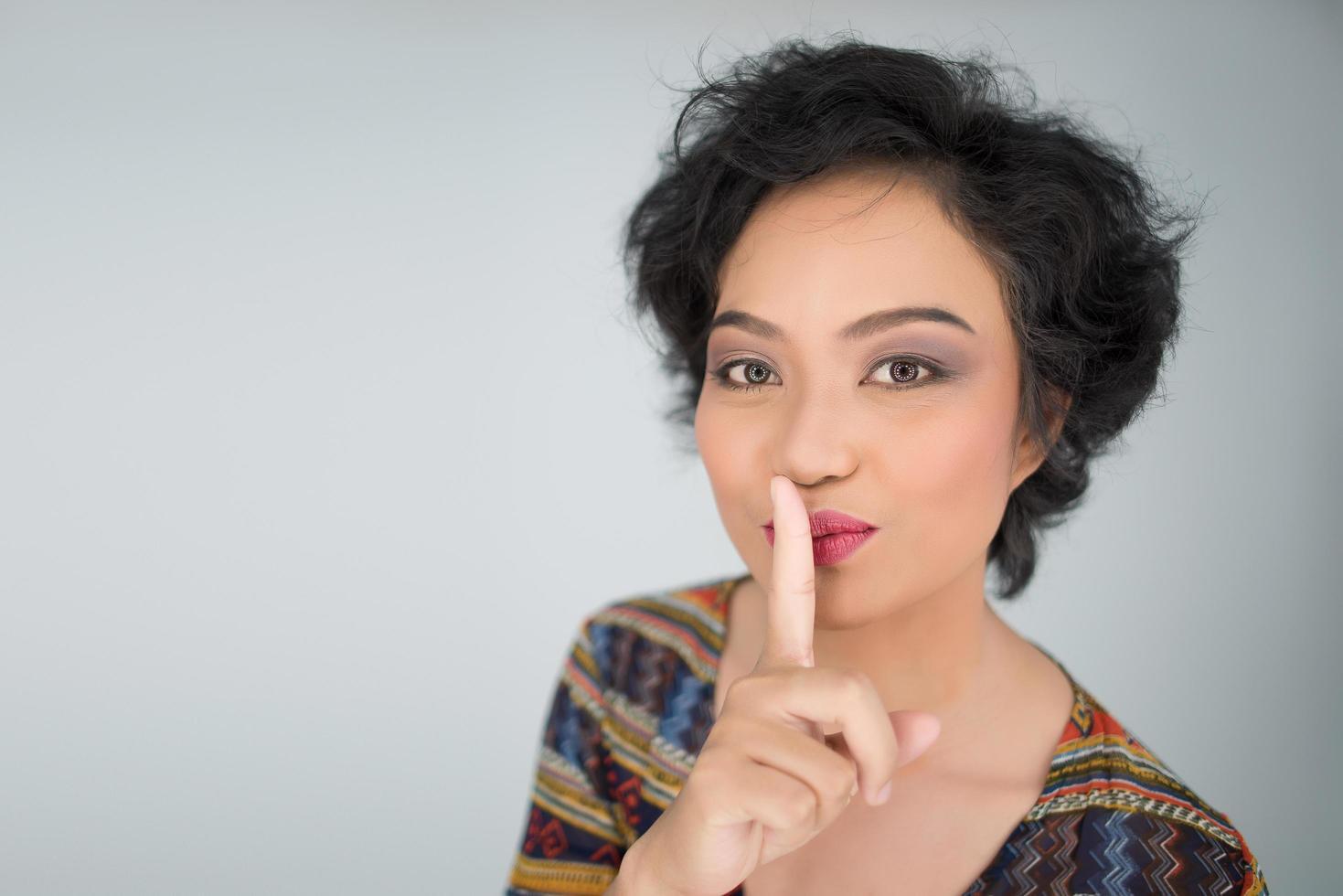 jonge vrouw maakt stil gebaar op witte achtergrond foto