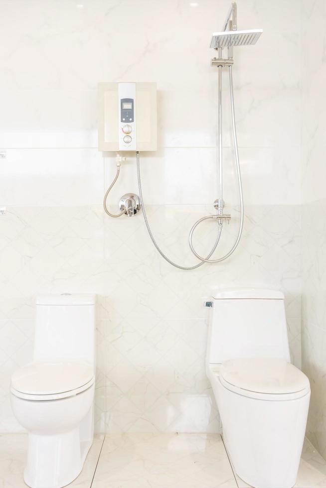badkamer interieur met douche. boiler en toilet op witte tegelsmuur foto
