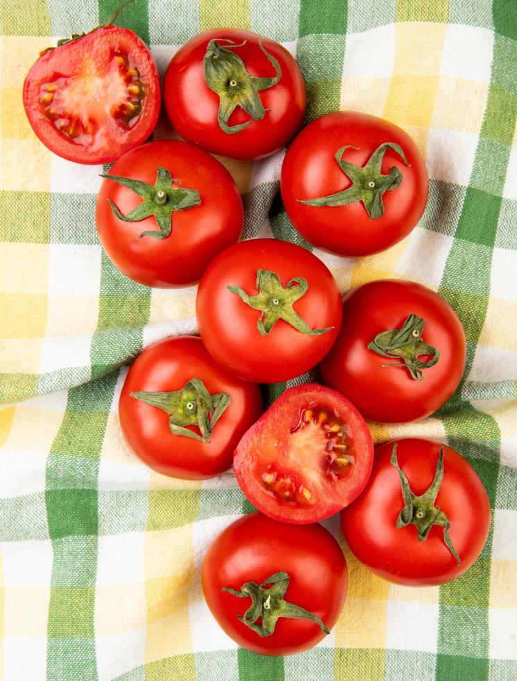 bovenaanzicht van gesneden en hele tomaten op geruite doek achtergrond foto