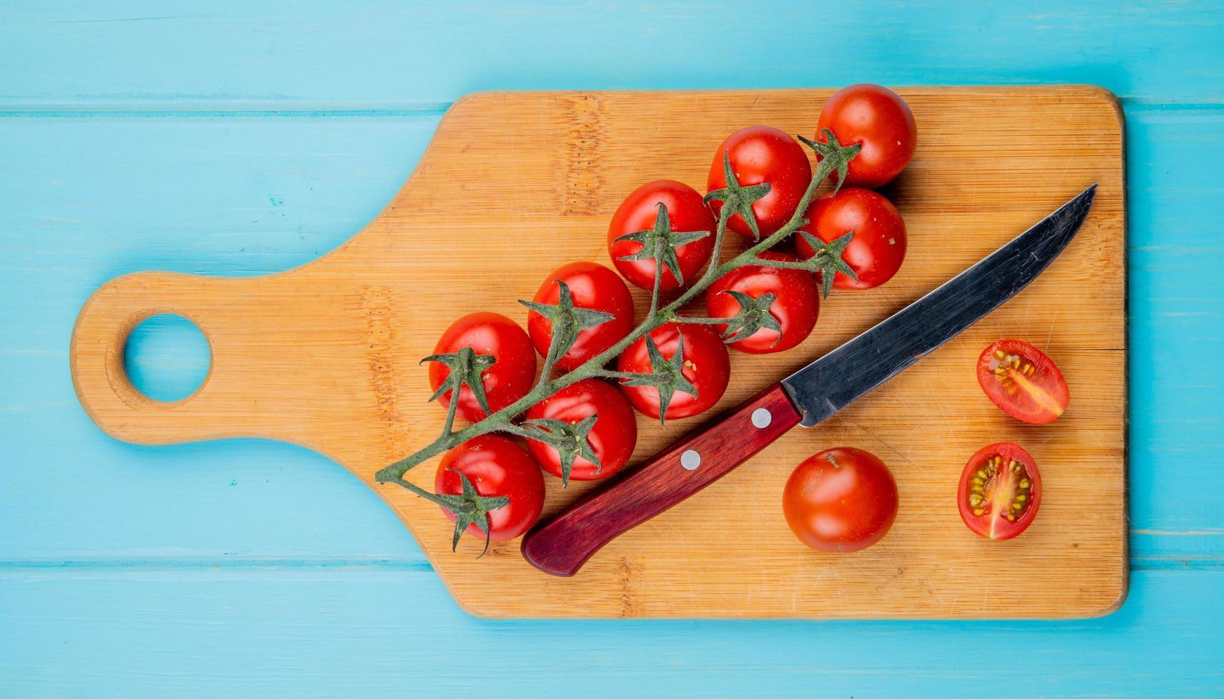 bovenaanzicht van gesneden en hele tomaten met mes op snijplank op blauwe achtergrond foto