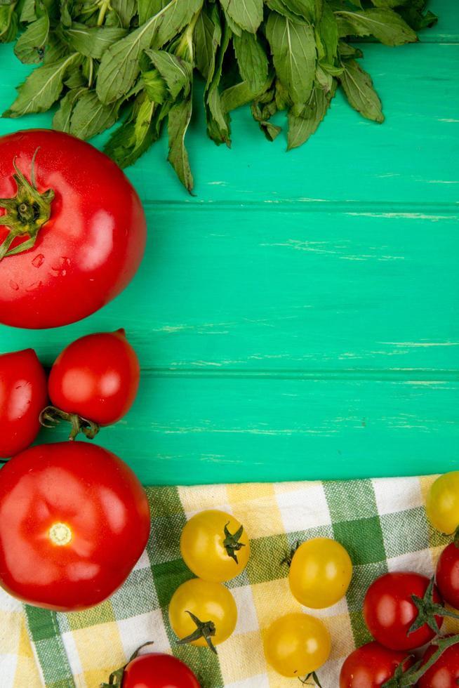 bovenaanzicht van groenten als groene muntblaadjes tomaat basilicum op groene achtergrond foto