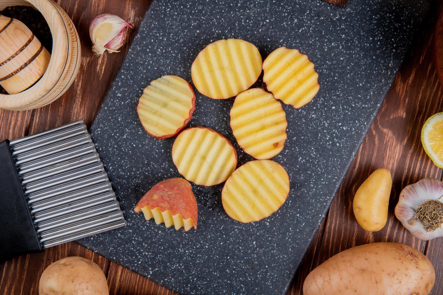 bovenaanzicht van gegolfde plakjes aardappelen op snijplank met hele citroen knoflook rond op houten achtergrond foto