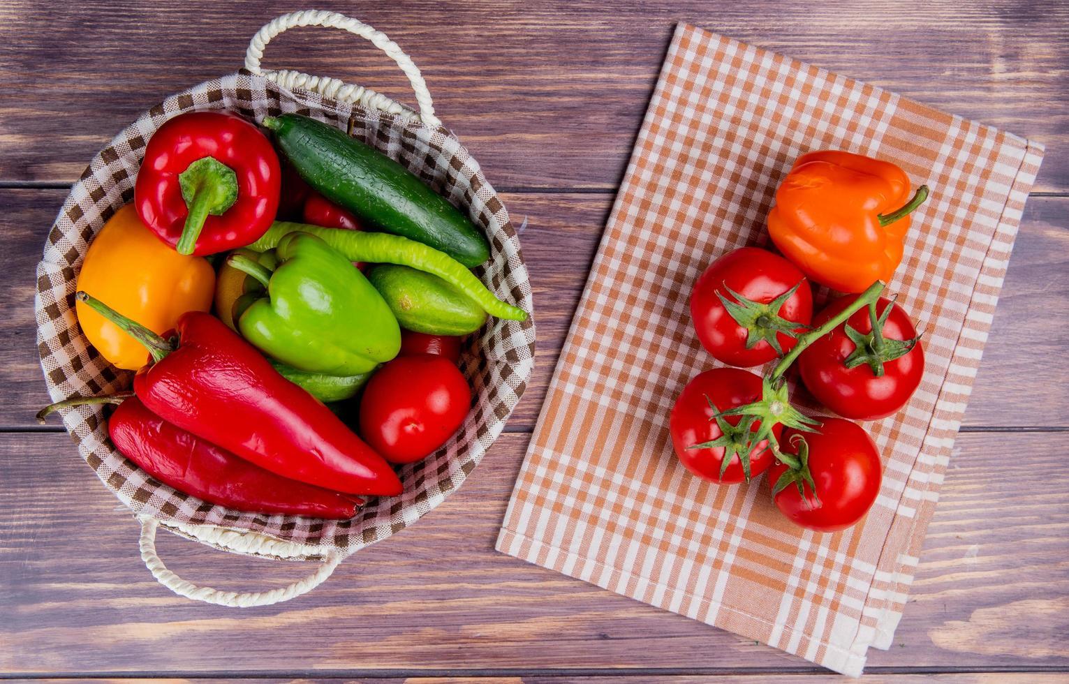 bovenaanzicht van groenten als komkommer paprika tomaat in mand met tomaten en peper op geruite doek en houten achtergrond foto