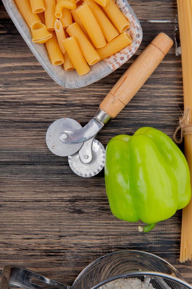 bovenaanzicht van ziti macaroni en peper op houten achtergrond foto