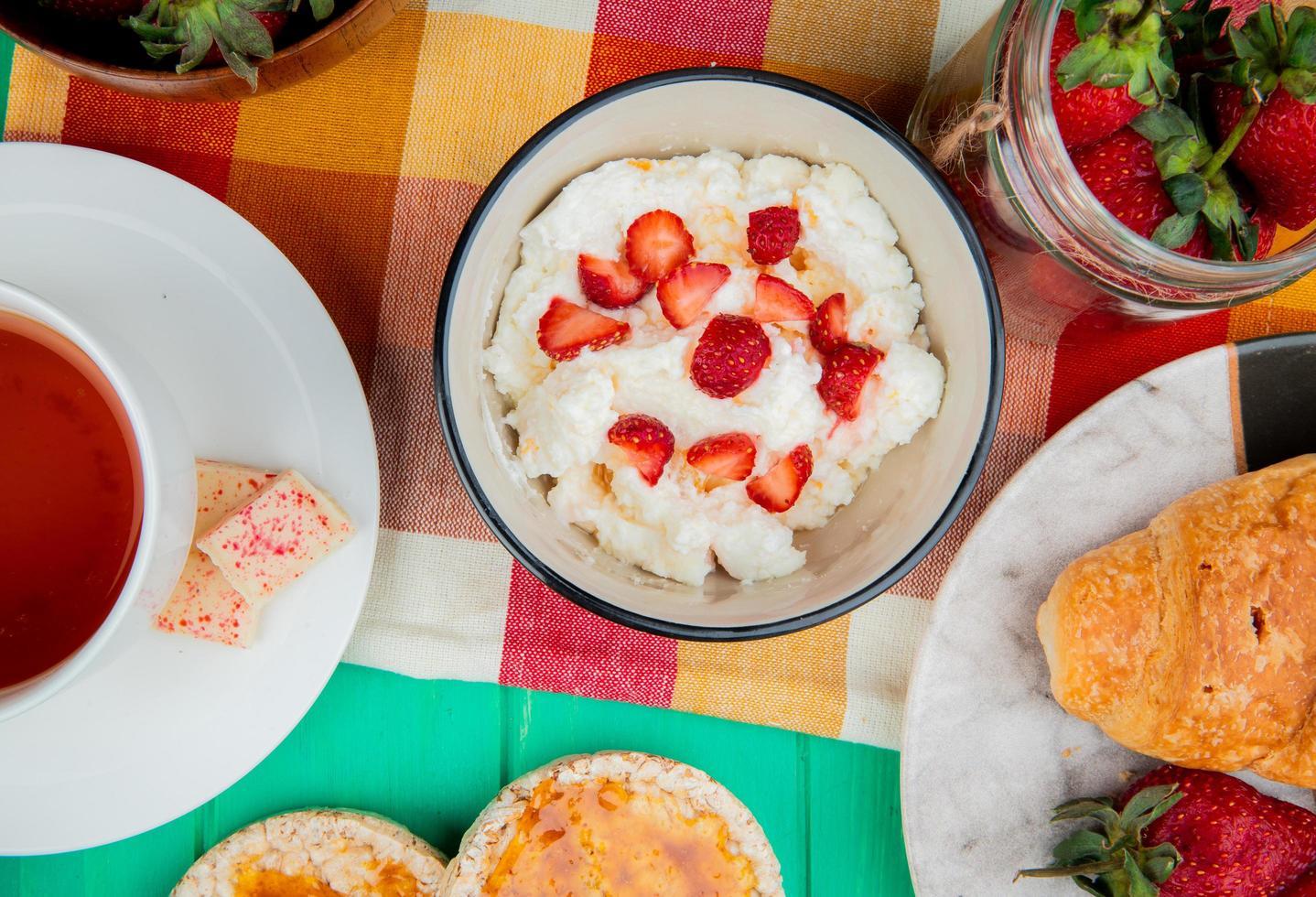 bovenaanzicht van kom kwark met aardbeien kopje thee knäckebröd halve maan roll op doek op groene achtergrond foto