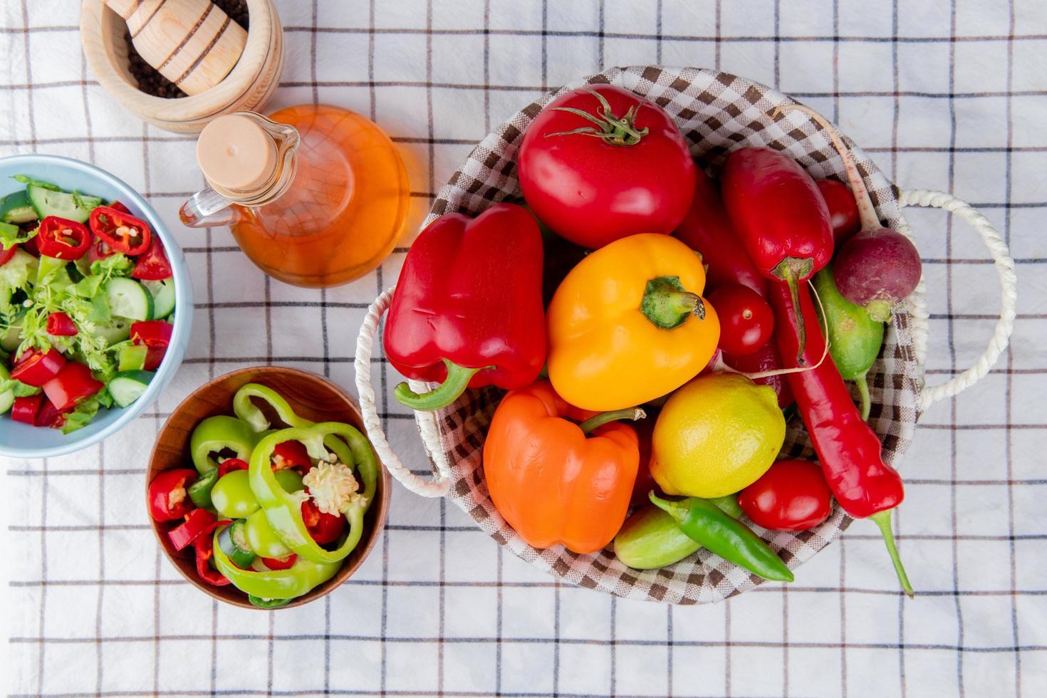 bovenaanzicht van groenten als paprika tomaat komkommer in mand met groentesalade gesmolten boter en knoflook crusher op geruite doek achtergrond foto