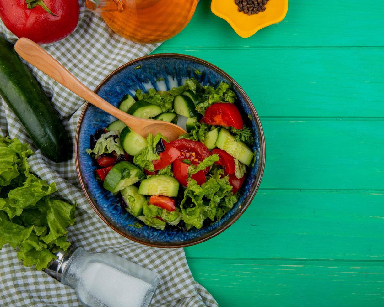 bovenaanzicht van groentesalade met tomatensla, komkommer, zout en zwarte peper op doek en groene achtergrond met kopie ruimte foto