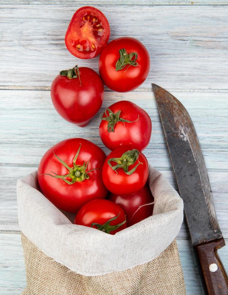 bovenaanzicht van tomaten morsen uit zak en mes op houten achtergrond foto