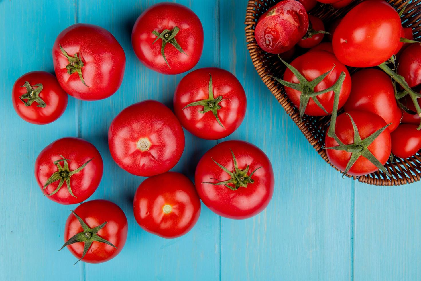 bovenaanzicht van tomaten met mandje tomaten op blauwe achtergrond foto