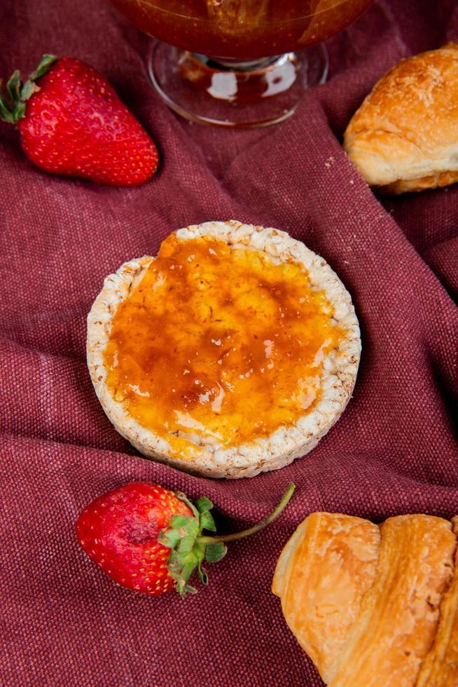 bovenaanzicht van knapperig knäckebröd en aardbeien met broodjes en jam op bordo doek achtergrond foto