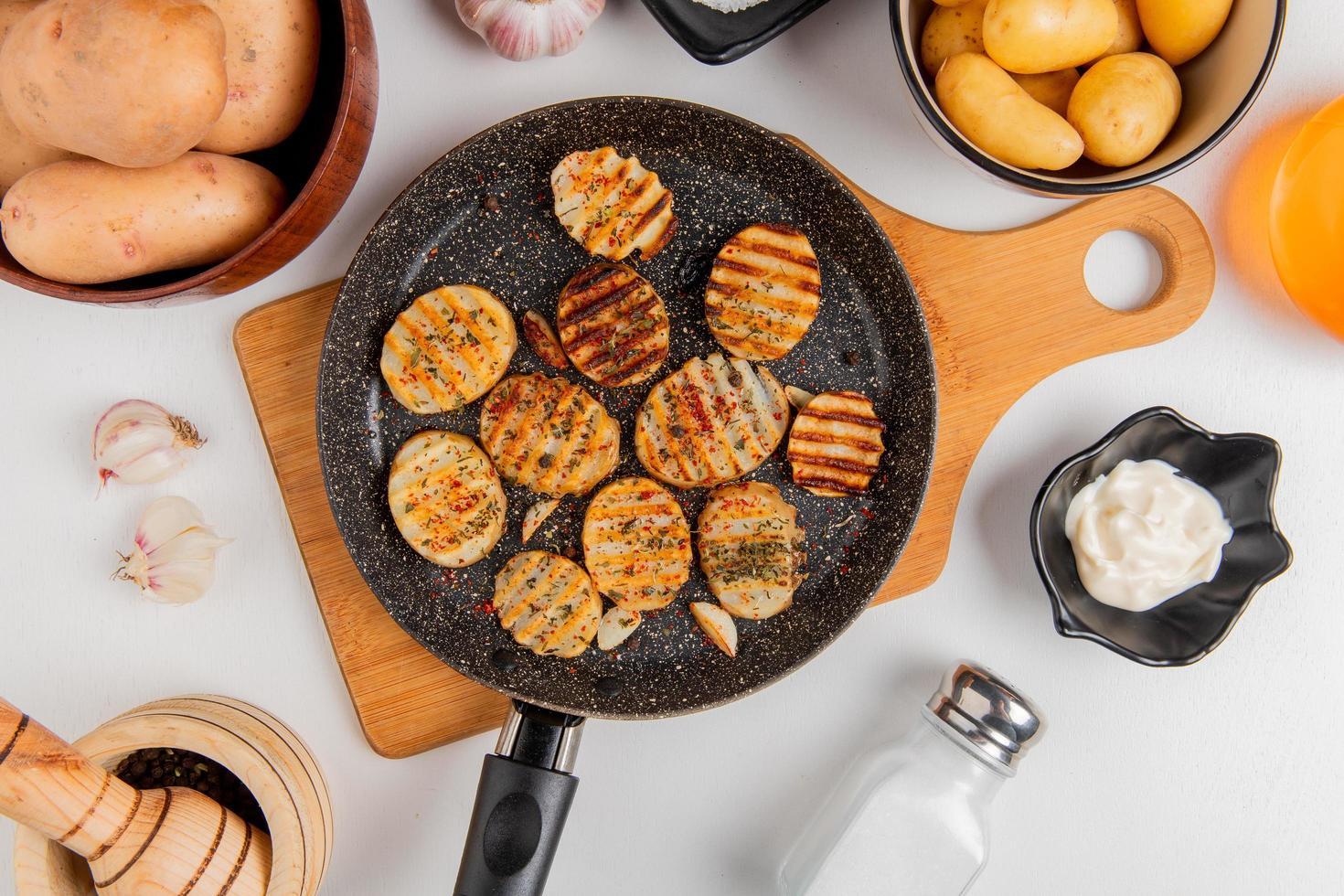 Bovenaanzicht van gebakken aardappelschijfjes in koekenpan op snijplank met ongekookte in kommen knoflookboter mayonaise zout en zwarte peper op witte achtergrond foto