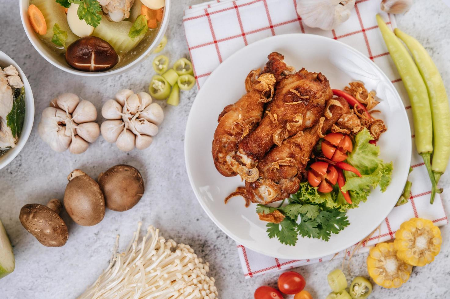 gebakken kippenpoten met tomaat, chili, gebakken ui, sla, mais en champignons foto