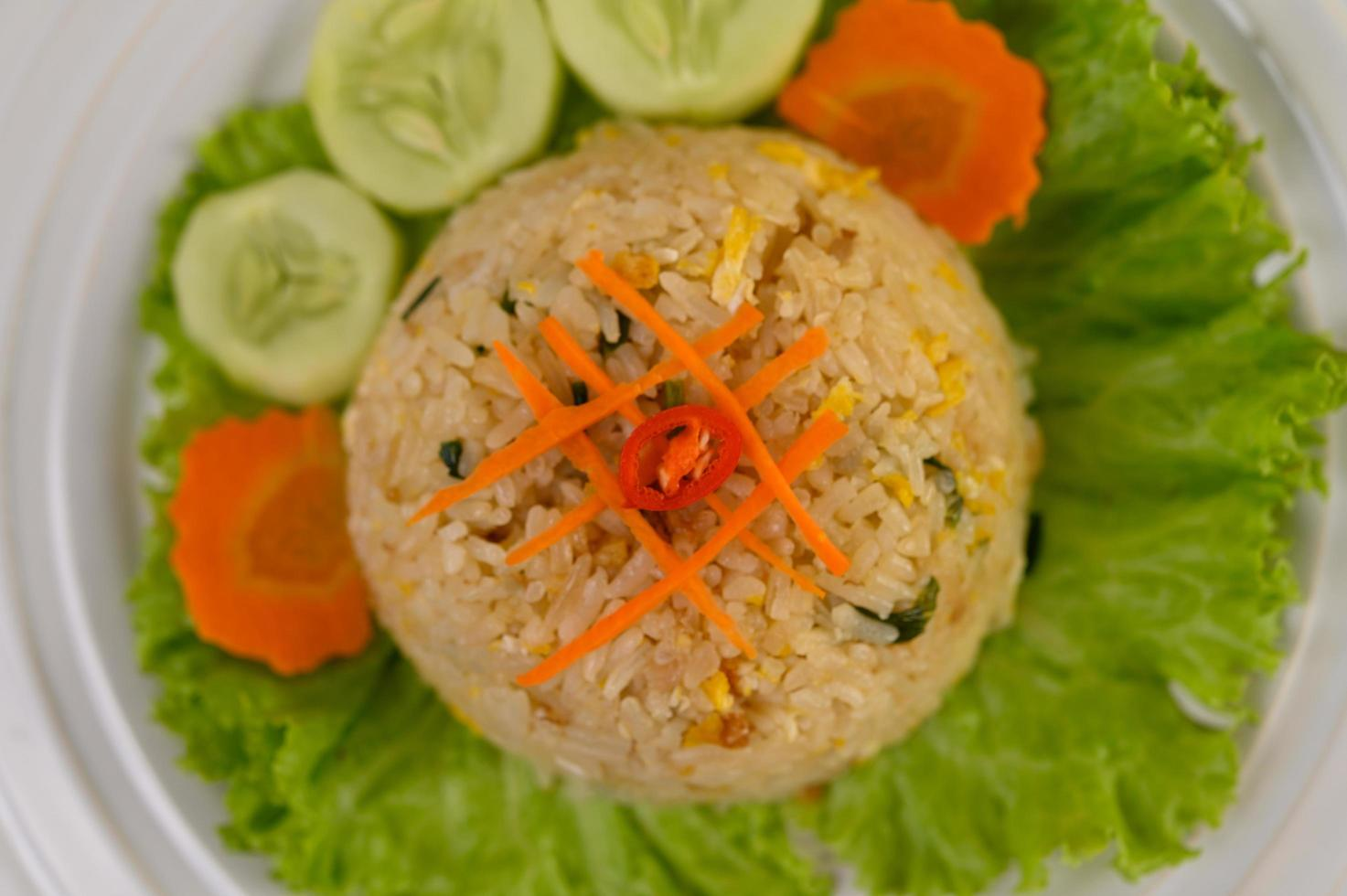 gebakken rijst op een witte plaat met sla en garnituur foto