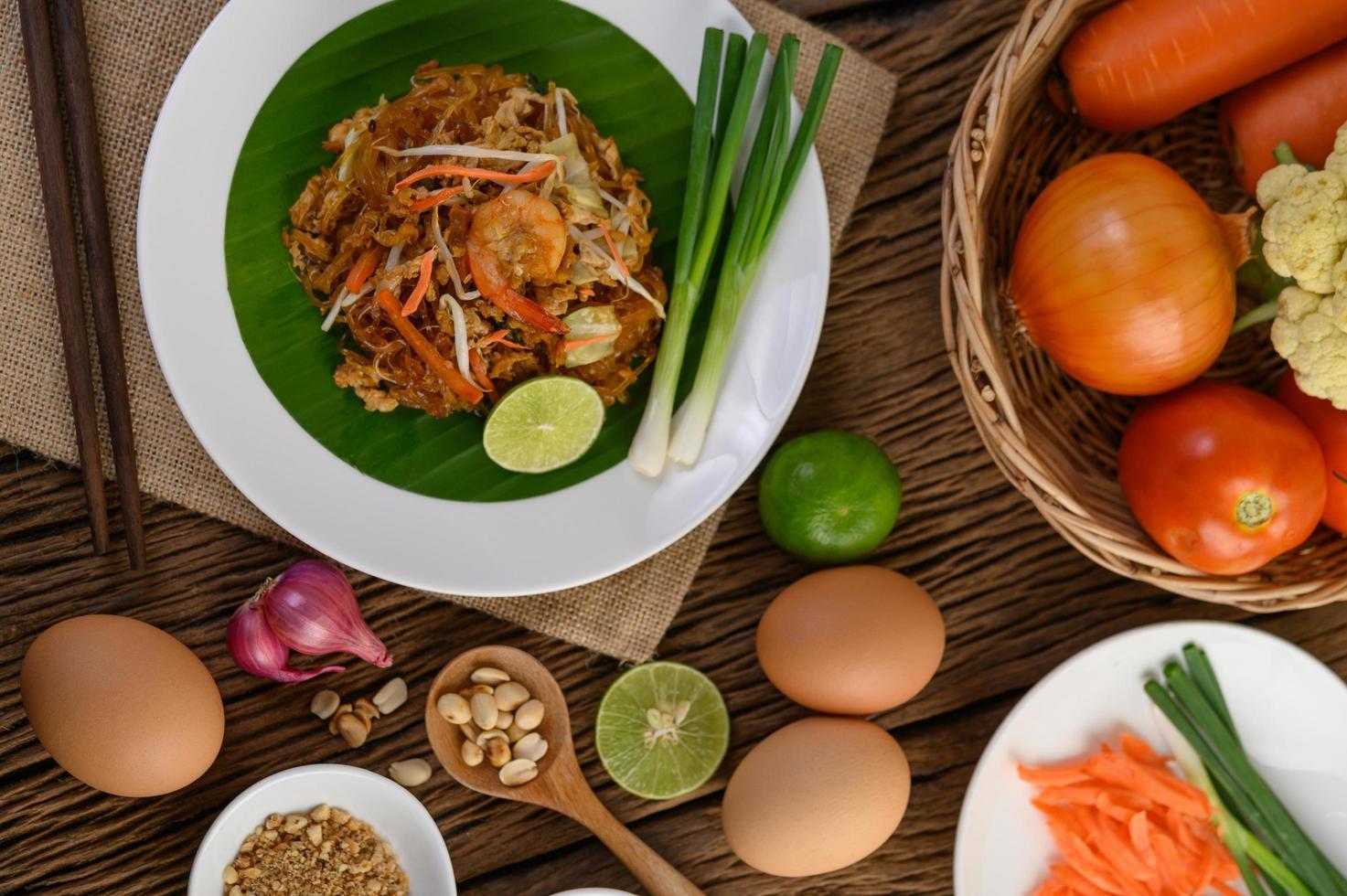 pad thai garnalen in een kom met eieren, lente-ui en kruiden foto