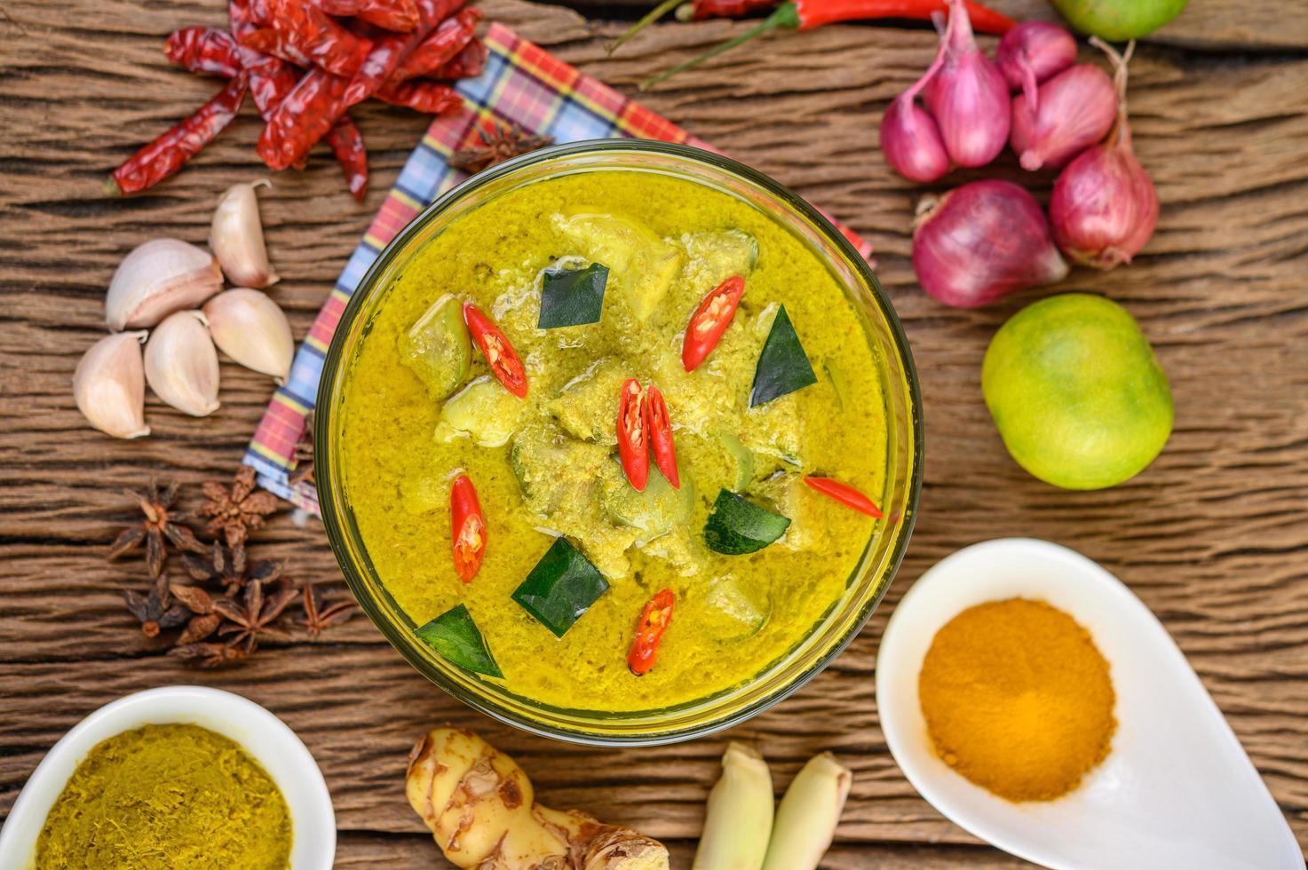 pittige groene curry in een kom met kruiden foto