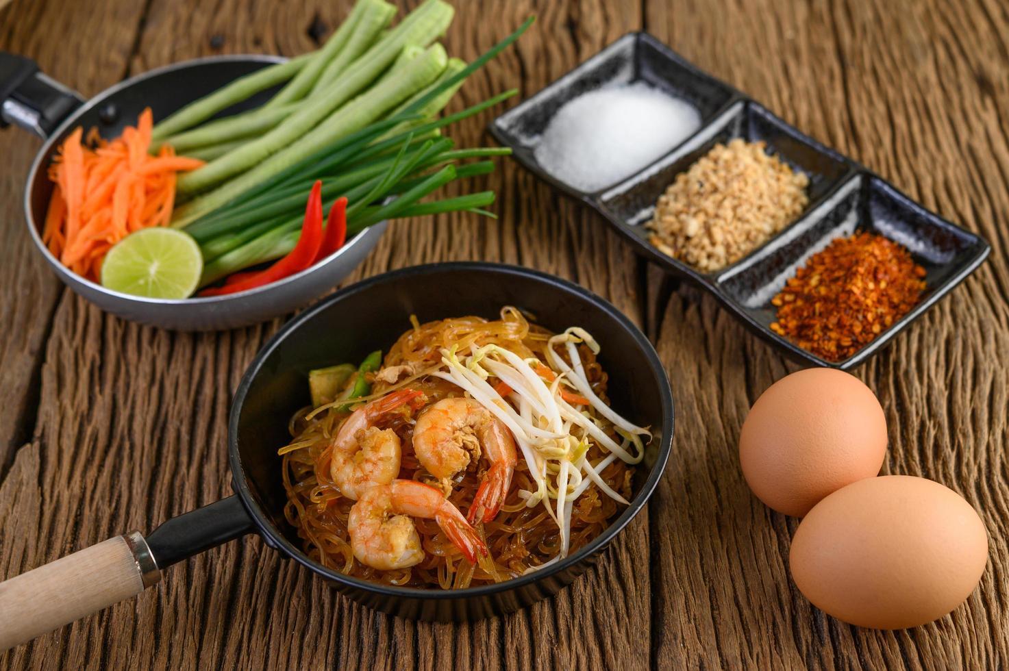 pad thai garnalen in een zwarte pan met eieren en kruiden foto