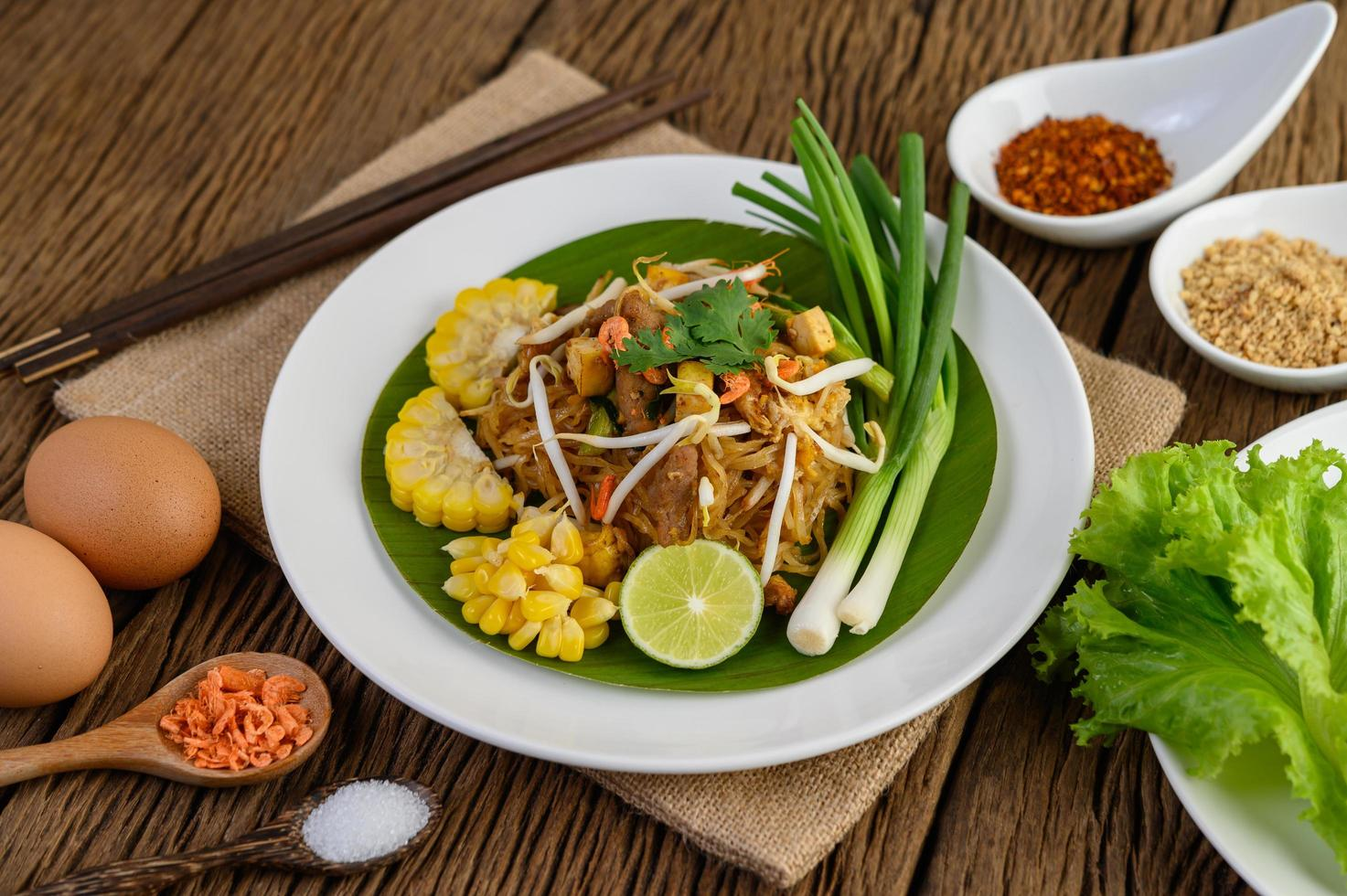pad thai met citroen, eieren en kruiden op een houten tafel foto