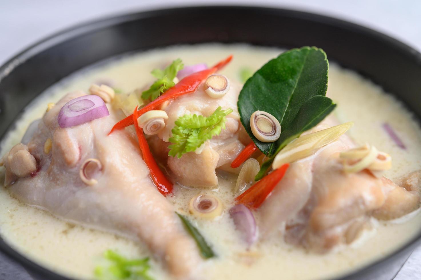 tom kha kai soep met kaffir limoenblaadjes, citroengras, rode ui, laos en chili foto