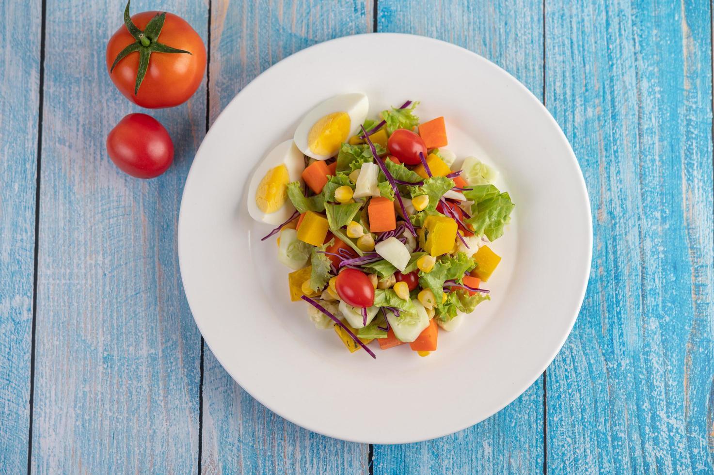 frisse salade op een witte plaat met een sandwich en tomaten foto