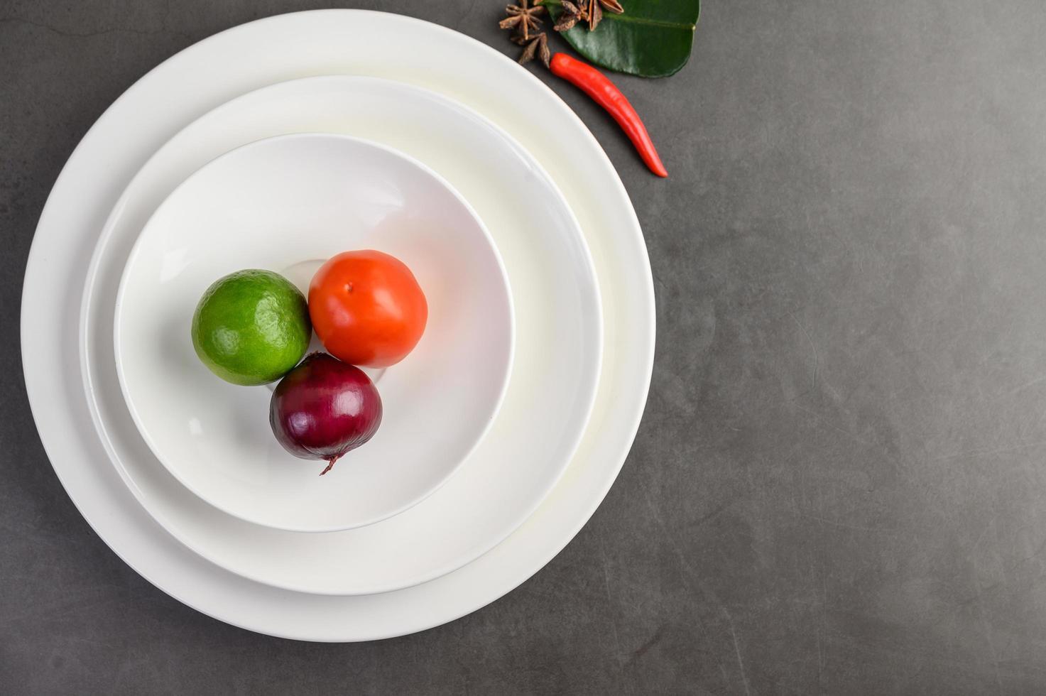 limoen, rode ui en tomaten op een witte plaat foto